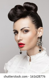 Close Up portrait of fashionable brunette model. Updo, vintage accessories. Makeup and hairstyle. Red lips, large earrings