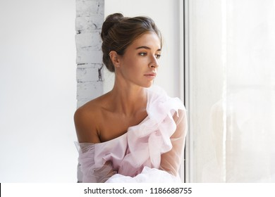Close up portrait of fashionable thoughtful woman wearing hair bun, earrings and expensive luxurious pink dress with one bare shoulder, sitting by the window and dreaming. Fashion, glamour and beauty