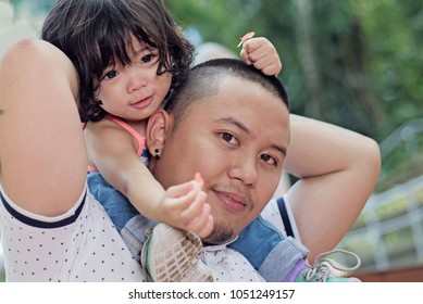 Close up portrait of a father carrying his daughter in his shoulder.