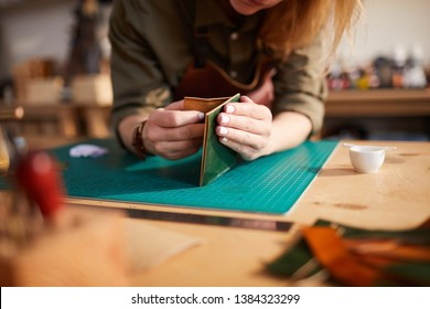 Close up portrait of female artisan making leather bag while working in shoemaking atelier, copy space