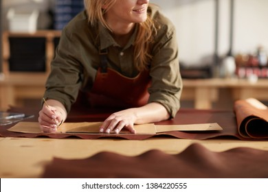 Close up portrait of female artisan working with leather in workshop, copy space