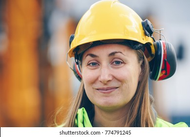Close up portrait of female construction worker in hard hat smiling