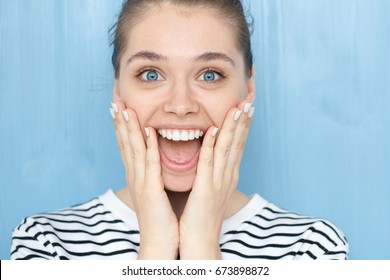 Close up portrait of female with Oh my god, WOW emotion expression. Pleasantly surprised smiling young girl with bugged blue eyes, holding hands on cheeks with widely open mouth in amazement