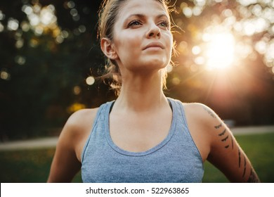 Close up portrait of fit young woman in sportswear standing outdoors and looking away. Confident fitness model in park.