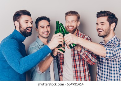 Close up portrait of four happy men friends, clinking their glasses of beer, smiling, alll are in casual outfits. They are fans of sports games as football, basketball, hockey, baseball