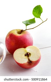 close portrait of fresh apple and sliced apple on white wooden table