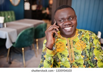 Close up portrait of friendly and smiling afro man in traditional yellow clothes sitting at restaurant and speak on phone.