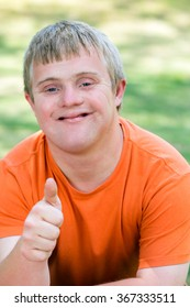 Close up portrait of friendly young man with down syndrome in orange t-shirt doing thumbs up.
