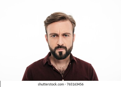 Close up portrait of frowning angry bearded man staring at camera isolated over white background