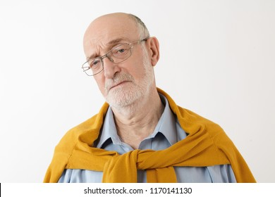 Close up portrait of frowning senior Caucasian bearded male with bald head posing in studio wearing stylish clothes and eyeglasses, looking at camera with mournful displeased facial expression