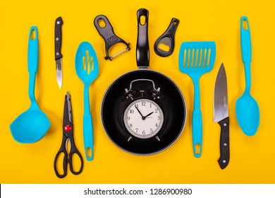 Close up portrait of frying pan with set of kitchen utensils on yellow background