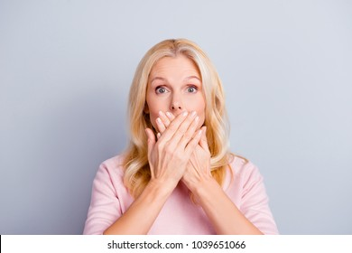 Close up portrait of funky curious cunning beautiful talkative gentle wondered astonished amazed lovely journalist grandmother grandma granny closes covers mouth isolated on gray background