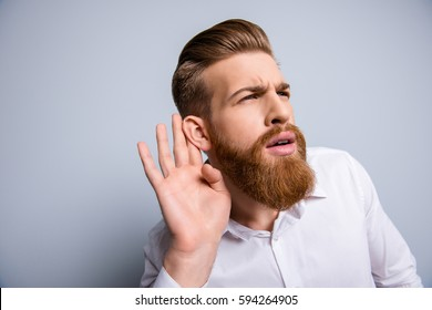 Close up portrait of funny bearded man holds hand near ear and trying to hear something