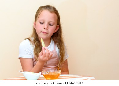 Close up portrait of funny lovely caucasian little girl eat apple with honey indoor. Jewish child dipping apple slices into honey on Rosh HaShanah the Jewish New Year.