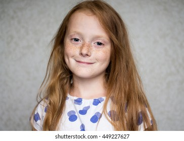 Close up portrait of a ginger smiling girl with freckles