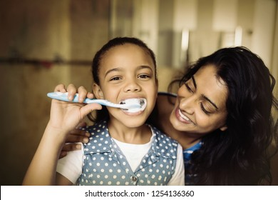 Close up portrait of girl brushing teeth with mother in bathroom