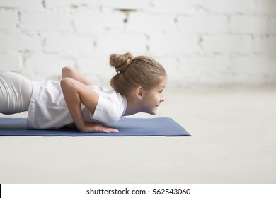 Close up portrait of girl child practicing yoga, standing in chaturanga dandasana exercise on blue mat, four limbed staff pose, Push ups, press ups, working out wearing sportswear, indoor white studio
