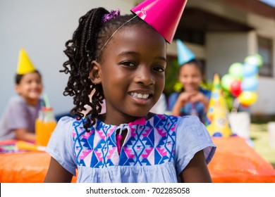Close up portrait of girl with friends in background during birthday party