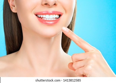 Close up portrait,  girl with healthy white teeth isolated on blue background, Woman smile. Teeth whitening. Dental care
