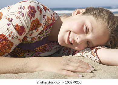 Close up portrait of a girl laying down on a golden sand beach.