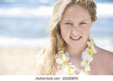 Close up portrait of a girl on the beach wearing a flower necklace and smiling.
