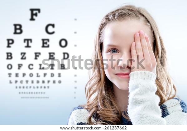 Nahaufnahme des Porträts von Mädchen, das das Auge mit der Hand betrachtet.Aus dem Fokustestdiagramm im Hintergrund.