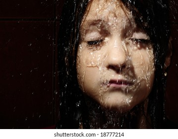 Close up portrait of a girl with water slopping on face