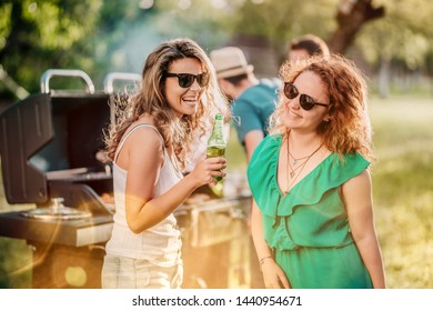 Close up portrait of girls drinking and laughing at backyard barbecue party