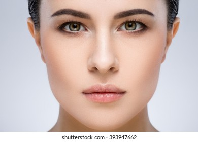 A close up portrait of girl's face with dark eyebrows, dark hair and light nude make-up, gray studio background, beauty photo.