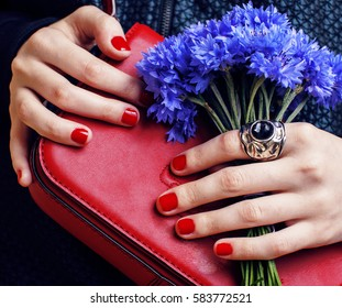 close up portrait of girls manicured hands holding small cute red handbag and cornflower bouquet, lifestyle concept flavor