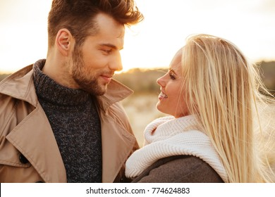 Close up portrait of a good looking couple in love hugging while walking along the beach