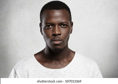 Close up portrait of good-looking serious African man with healthy clean skin wearing white casual t-shirt posing isolated against gray studio wall with copy space for your promotional content