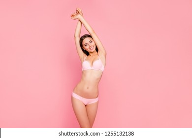 Close up portrait of gorgeous gentle glad her she girl standing with hands up showing result on underarms removing hair procedure wearing pale pink underwear isolated on pink background
