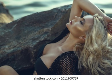 Close up portrait of gorgeous glam tanned blond woman with closed eyes wearing black swimsuit and summer tunic relaxing and bathing in the sun lying on the large stones at the seaside. Copy space