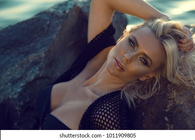 Close up portrait of gorgeous glam tanned blond woman wearing black swimsuit and summer tunic relaxing on the large stones at the seaside. Copy space