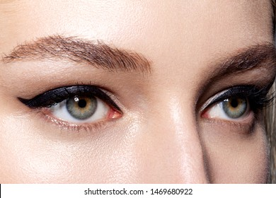 Close up portrait of gorgeous green lady eyes with professional visage and brown incredible eyebrows. Girl calmly looking away. Beauty and cosmetics concept
