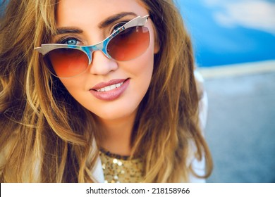 Close up portrait of gorgeous woman with big blue eyes perfect skin full lips and white teeth, posing near deep blue sea,smiling and looking on camera,wearing trendy vintage golden cat eye sunglasses.