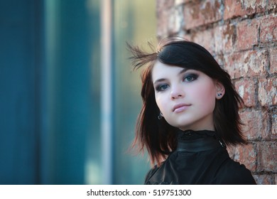 Close up portrait of gothic teenager girl on wall bricks background