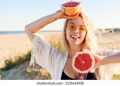 Close up portrait of graceful blonde woman with candid smile holding citrus fruits in hands and having fun on amazing California coast . Diet and healthy food concept.