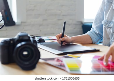 Close up portrait of graphic designer hands retouching images using graphic drawing tablet in special program. Laptop,monitor, and color palette. Retoucher workplace in photo studio. Creative agency.