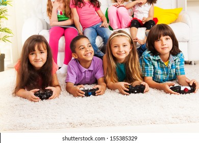 Close portrait of a group of diversity looking kids, boys and girls playing videogame, laying on the floor in kids room