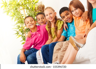 Close portrait of group of diversity looking kids sitting on the couch at home, hugging, smiling and laughing