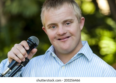 Close up portrait of handicapped boy holding microphone outdoors
