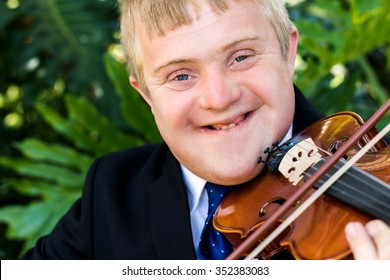 Close up portrait of handicapped violinist playing violin against green background.