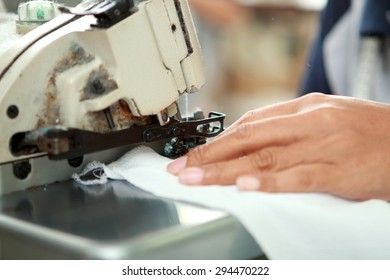 close up portrait of hands of worker and industrial sewing machine