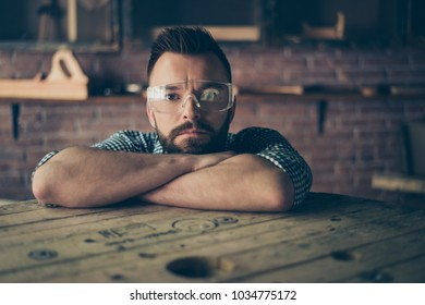 Close up portrait of handsome bearded confident concentrated serious joiner wearing protective safety glasses for work, he is leaning on the folded arms with his head and thinking over new project