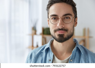 Close up portrait of handsome bearded man wears round spectacles, has appealing appearance with beard and mustache, dressed in fashionable clothes, stands against cozy interior. Student poses indoor