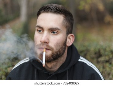 close up portrait of a handsome blond bearded white  guy with blue eyes and ear piercing smoking a cigarrete and looking away with serious face wearing a sport black and white hoodie