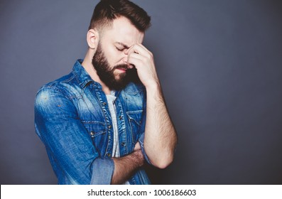 Close up Portrait of a handsome confident bearded man with a severe headache