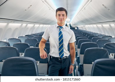 Close up portrait of handsome confident steward posing at the photo camera near the cozy chair of passenger aircraft